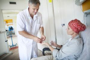 Arzt gibt Patientin Medkamente bei Chemotherapie