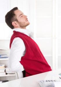 Mann mit Rückenschmerzen sitzend im Büro hat Morbus Bechterew