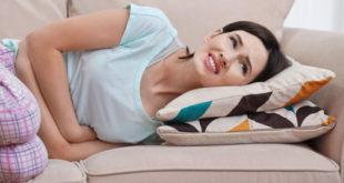 Frau mit Bauschmerzen wegen Gastritis auf dem Sofa