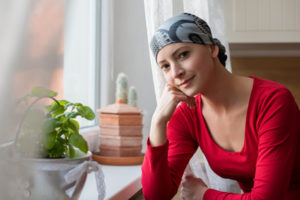 Junge Frau Krebspatient sitzt vor dem Fenster