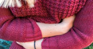 Junge Frau verschränkt Arme vor dem Bauch